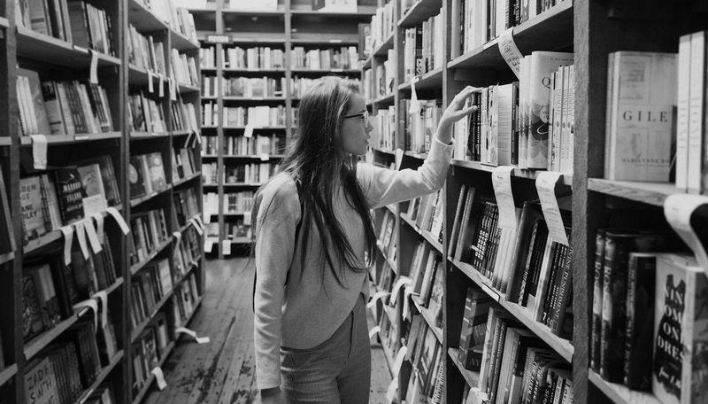 Jazykovedkyňa v knižnici si prezerá knihy